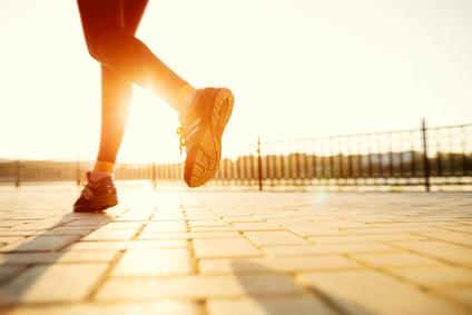 Runner feet running on road closeup on shoe. woman fitness sunrise jog workout welness concept.